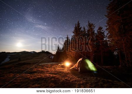 Tourist Camping Near Forest In The Night. Illuminated Tent And Campfire Under Beautiful Night Sky Fu