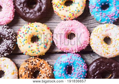 assorted donuts with chocolate frosted pink glazed and sprinkles . Top view