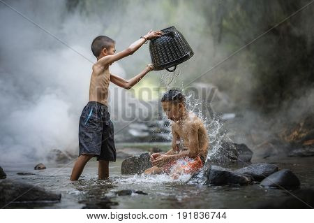 Portrait of Asian boy fisherman with waterfall in outdoorsChildrens playing in the creek water happilyChildren fishing in the riverThe boys are enjoying playing the streamAsian boyAsian Children