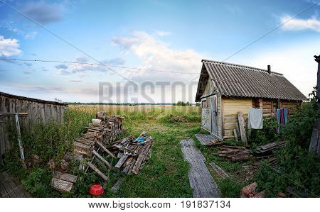 Wooden house or Bathhouse or Barn in the village, cloudy sky, sunny day.