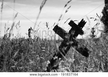 Old, wooden cross on gravestone among grass blades. Black and white