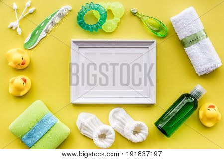 Baby care with bath cosmetic set, frame, ducklings and towel on yellow background top view mockup