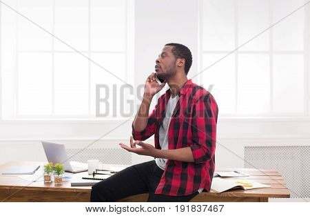 Hard business call. Disappointed african-american businessman in white has mobile phone talk in modern white office interior.