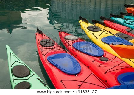 Red Teal Yellow and Orange Kayaks float on water of teal color