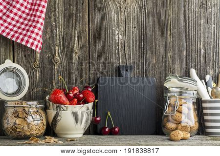 Simple kitchen still life on a background of a wooden wall on a shelf with cutlery, tools, marble bowls andstrawberry, cherry . The concept of home comfort food and comfort.