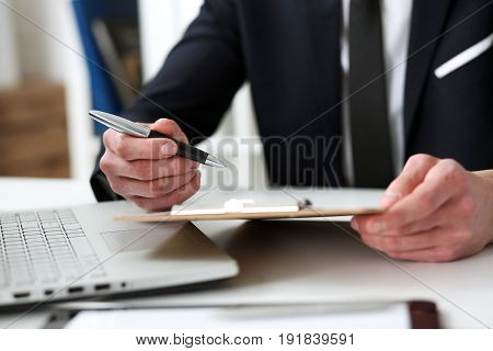Hand Of Businessman In Suit Signing Document