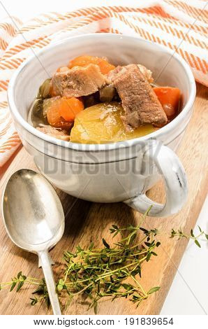 traditonal irish stew in a grey mug with thyme