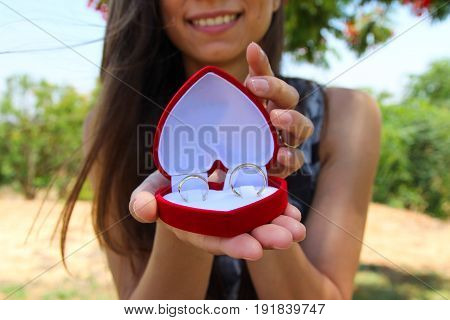 Women Hands With A Velvet Red Box With A Pair Of Gold Wedding Rings