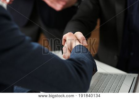 Two Businessman Shake Hands As Hello In Office Closeup