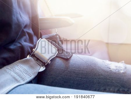 Fastened airplane seat belt and light coming from plane window. Woman sitting in aeroplane waiting for take off.