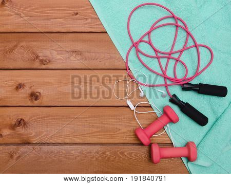 Dumbbells and skipping rope on wooden table background. Fitness lifestyle concept.
