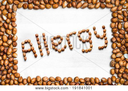 Allergy written with peanuts and surrounded with nut frame. Word and text made from nuts. Groundnuts on white wooden table or board with border. Allergic reaction and nutrition problem. Top angle view