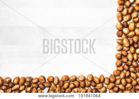 Peanut corner background. White wooden board or table with nut frame or border. Groundnut backdrop and template with copy space.