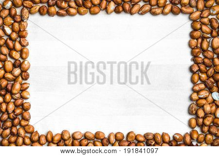 Peanut frame background. White wooden board or table surrounded with nut border in the shape of a rectangle. Groundnut backdrop and template with copy space.