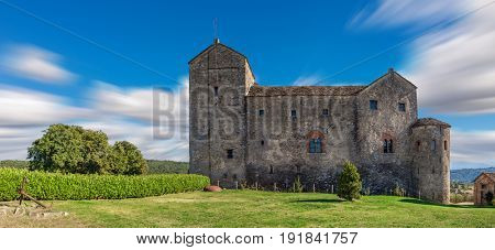 View of old medieval castle under blue sky in Piedmont, Northern Italy (panorama).