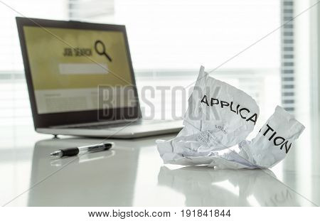 Out of work and frustration concept. Ripped job application paper on home office table with laptop and employment search engine. Problems, anger and sadness from unemployment. Depressed applicant.