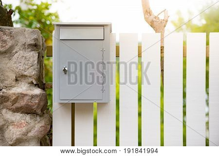 Post box on white wooden fence. Sweden Scandinavia Europe.