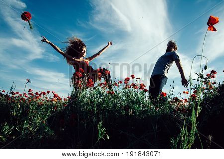man and girl with long curly hair in red dress with flower bouquet dancing in field of poppy seed with green stem on blue sky background summer drug and opium couple in love