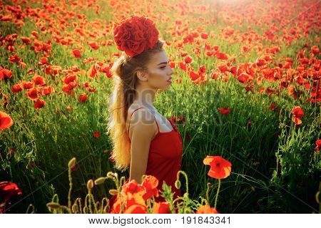 girl with long curly hair in red dress hold flower bouquet in field of poppy seed with green stem on natural background summer spring drug and love intoxication opium
