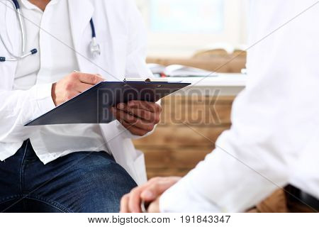Male Medicine Doctor With Clipboard Pad In Hands Examine Patient