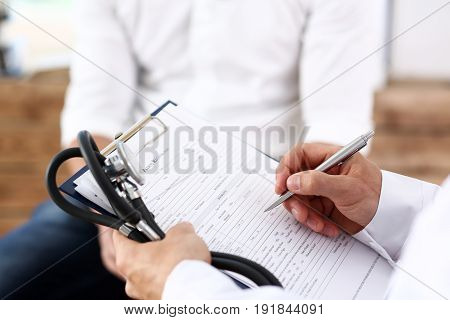 Male Doctor Hand Hold Silver Pen Filling Patient History List