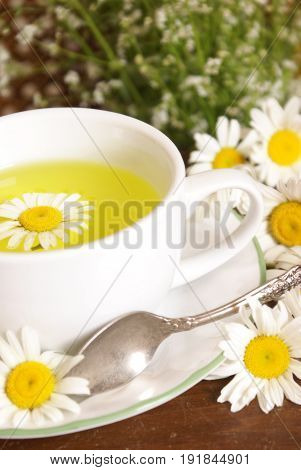 A lovely fresh cup of Chamomile tea with a silver spoon.
