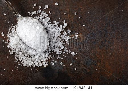 Sea salt in stainless steel spoon over rusty background