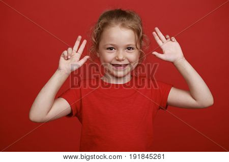 Little girl shows off her red-painted palms - smiling little student girl showing painted hands at school, summer outdoors
