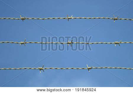 metal fence barbed wire on blue sky closed boundary