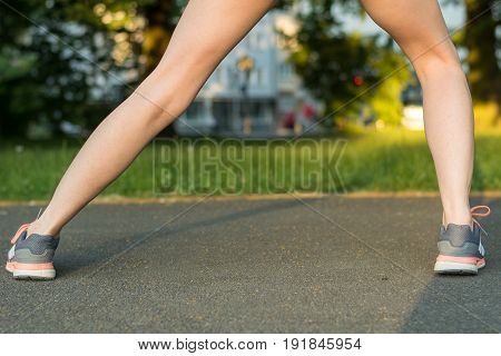 Runner Stretches Leg On Tarmac With Running Shoes From Behind