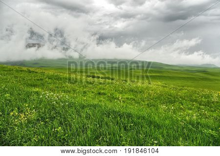 Pre-storm weather in the field. Beautiful dramatic landscape with low dark clouds and a green grass