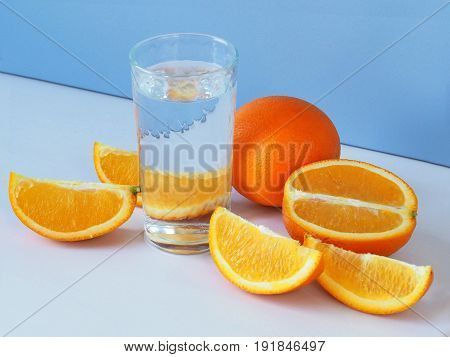 Oranges and a glass of water. Blue background.