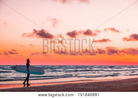 Girl with surfboard on beach at sunset or sunrise. Surfer and ocean