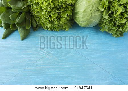 Green vegetables lettuce and herbs at border of image with copy space for text. Top view. Cabbage spinach dill and lettuce. Green vegetables on a blue background.