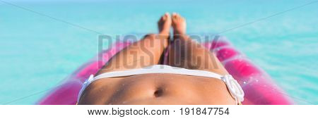 Luxury travel caribbean tropical beach vacation banner panorama bikini woman sunbathing on air mattress. Legs suntan girl relaxing on inflatable swimming pool bed floating in turquoise ocean water.