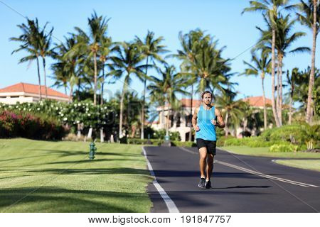 Running man sports fitness athlete runner jogging on residential road in tropical city. Summer workout person training cardio outdoors.