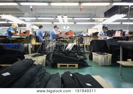 MOSCOW - FEB 21, 2017: People in workshop with leather and suede cutting machines in Ralf Ringer factory. Company production is 1,5 million pairs per year