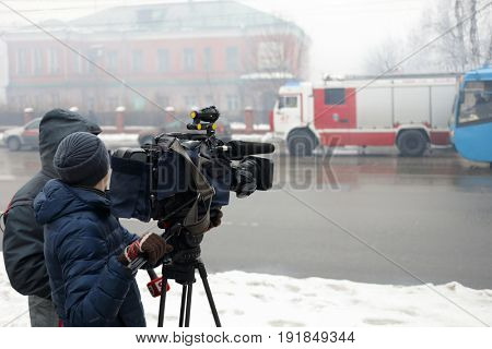 MOSCOW - DEC 31, 2016: Reporters work for destructive fire place, firefighters truck in smoke
