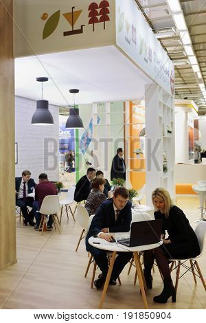 MOSCOW - MAR 16, 2017: People at tables at real estate exhibition in Central House of Artists, 200 companies took part in exhibition