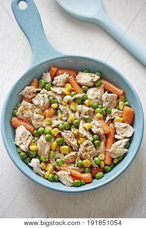 Chicken with corn, peas and carrots on frying pan