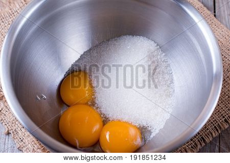 Egg yolks and sugar in a metal bowl