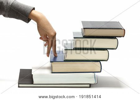 Fingers stepping on books as a concept of the progress in education
