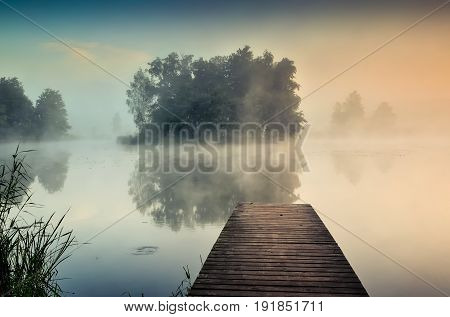 Morning misty landscape on the lake. Wooden pier and island with trees on the lake.
