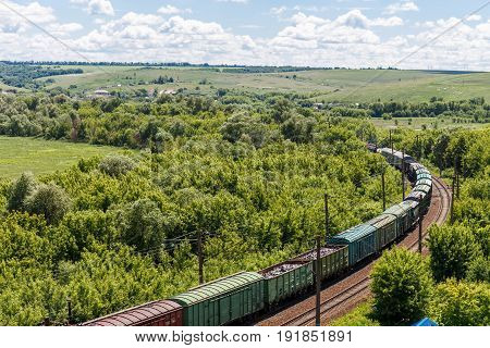 The freight railroad train rides through fields and hills amidst green meadows and trees, Freight transportation concept