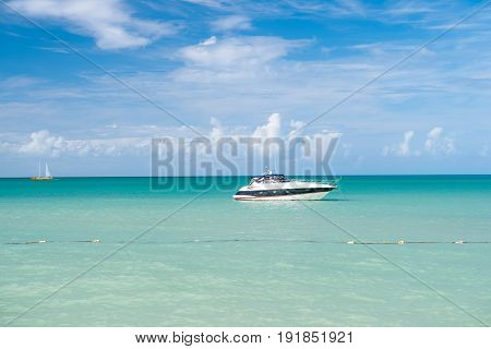 Exotic beautiful marine beach of Antigua St. Johns with yacht boat on blue water and sky with small clouds