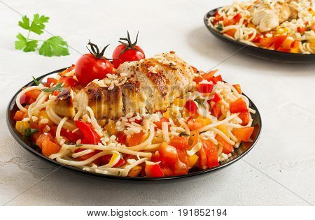 Baked boneless skinless chicken breasts and pasta salad with fresh vegetables on the black plates.