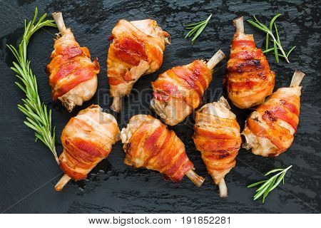 Bacon wrapped chicken drumsticks on a black stone background top view.