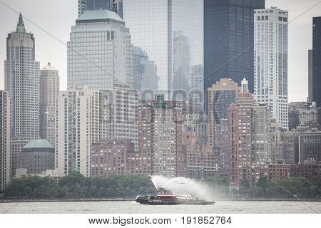 Eric McAllister harbor tugboat sprays water as it passes the Freedom Tower and World Trade Center Financial District at the Parade of Ships at start of Fleet Week New York, JERSEY CITY NJ MAY 24 2017.