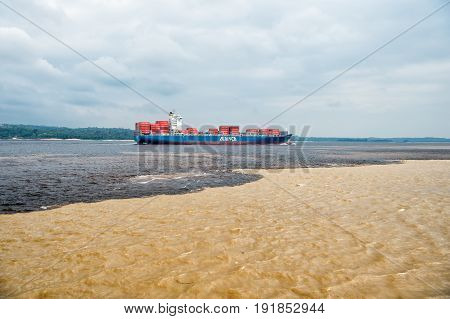 Manaus Brazil- Decemcer 4 2015: water meeting in Brazil -amazon river with rio del negro clean and dirty river water with different streams. Cargo ship paasing water meeting