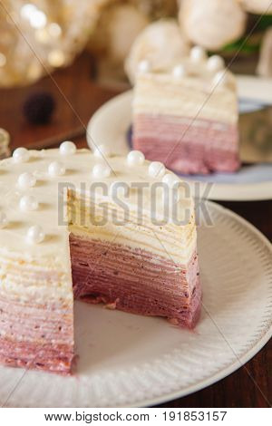 Vanilla and blueberry ombre cake in pink colors with berries